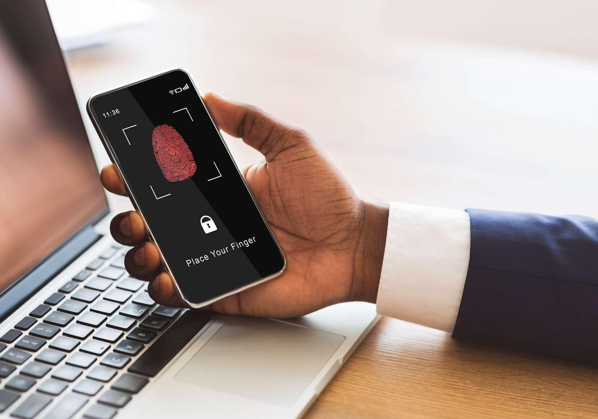 Man holding phone with fingerprint scanning smartphone app
